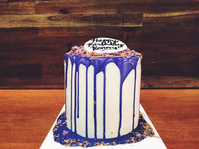 Ube cake with Coconut Buttercream topped with a purple dripped white chocolate ganache, cake crumbs, toasted coconut & a fondant topper.